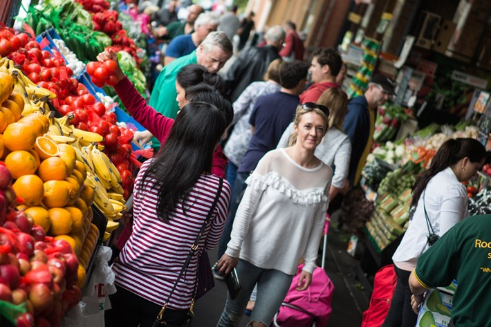 woman walking past fruit and vegetable stall display
